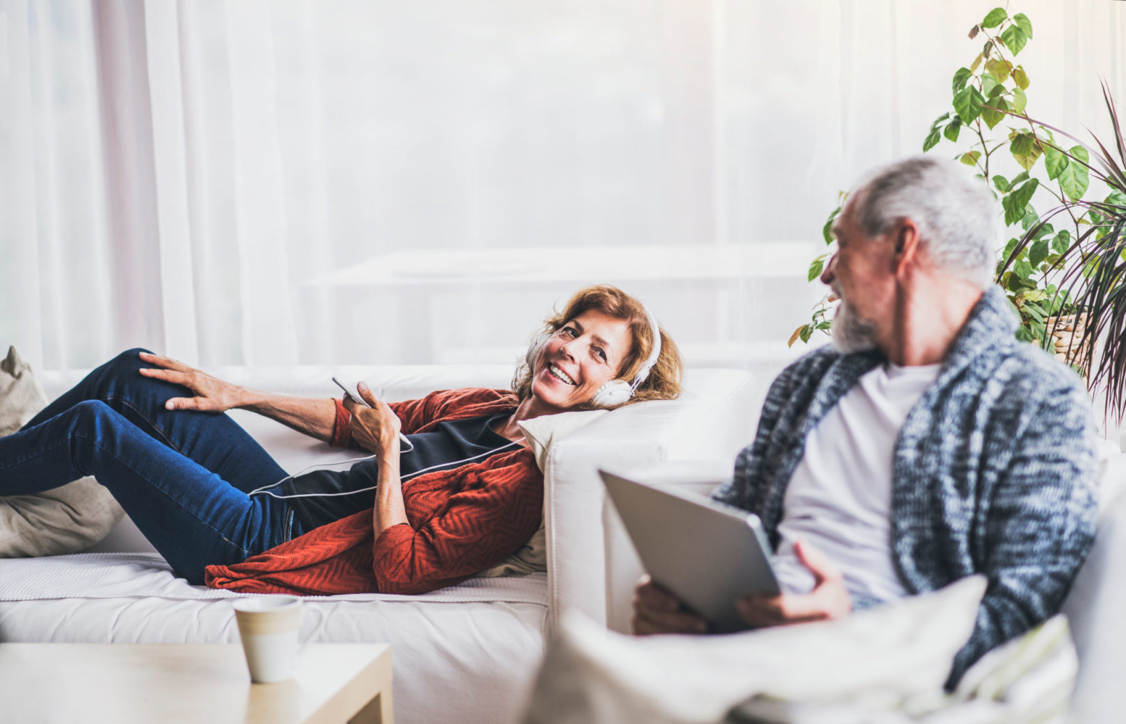 Senior couple with tablet and smartphone relaxing at home.