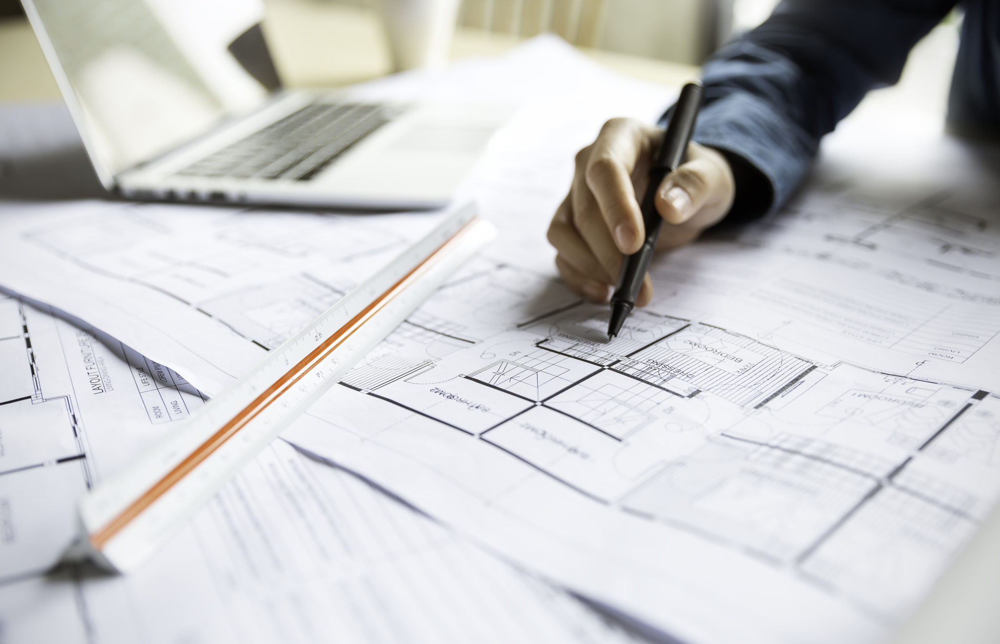 Close up woman hand working of Architect sketching project on blueprint at site construction work. Concept of architect, engineer in the office desk construction project